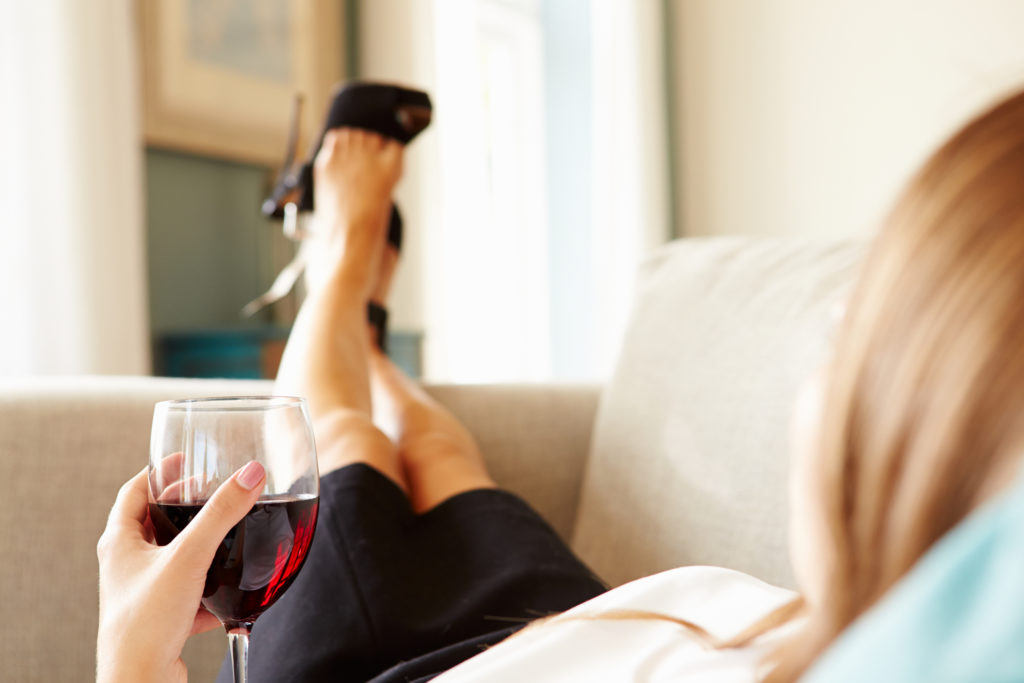 Woman drinking glass of wine after work