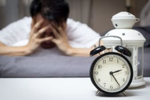 Frustrated man in front of alarm clock