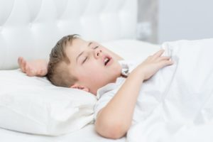 mall boy in white bed snoring due to sleep apnea