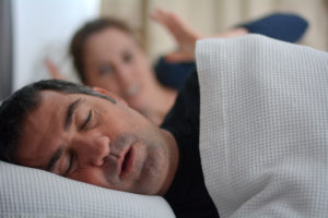 Man sleeping on side snoring; wife in background