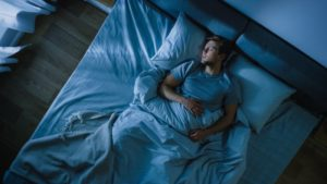 Far shot of man in bed with sleep apnea