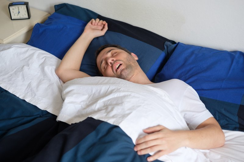 Man with sleep apnea sprawled out in bed